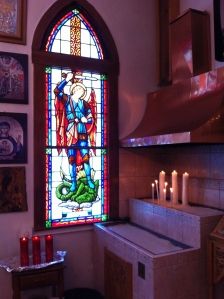 To the right side of the entrance doors- a stained glass window with his image and an area where one can light candles